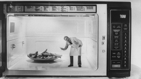 Chemist Robert Schiffmann, seen in miniature w. lab coat & stethoscope leaning toward plate of french fries browning in microwave, thanks to his research in making foods crisp in microwave cooking.  (Photo by Evelyn Floret//Time Life Pictures/Getty Images)