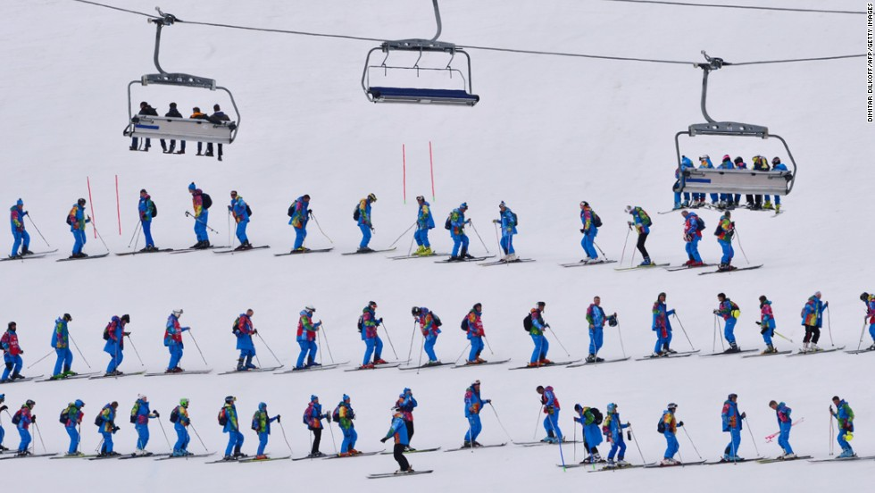 Volunteers flatten the snow prior to the start of the slalom portion of the men's super-combined on February 14.