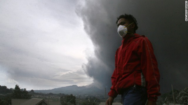 A resident evacuates under a massive plume of hot ash clouds spewing from Mount Kelud volcano as seen from Malang district in East Java province on February 14, 2014.