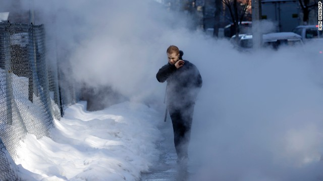 A pedestrian walks through a cloud of steam on a snowy street in New York, Friday, Feb. 14, 2014. Commuters faced slick roads on Friday after yet another winter storm brought snow and ice to the East Coast, leaving at least 24 people dead. (AP Photo/Seth Wenig)