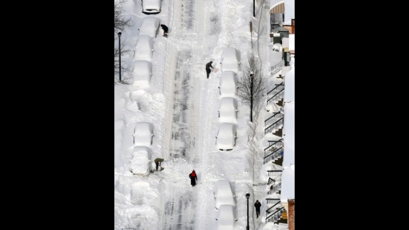 People dig out vehicles buried in snow in Albany, New York, on February 14.