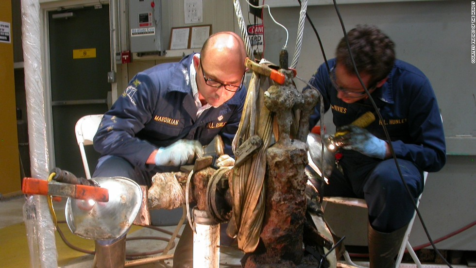 Paul Mardikian, left, senior conservator, and Philippe de Vivies remove material from a piece of the submarine.