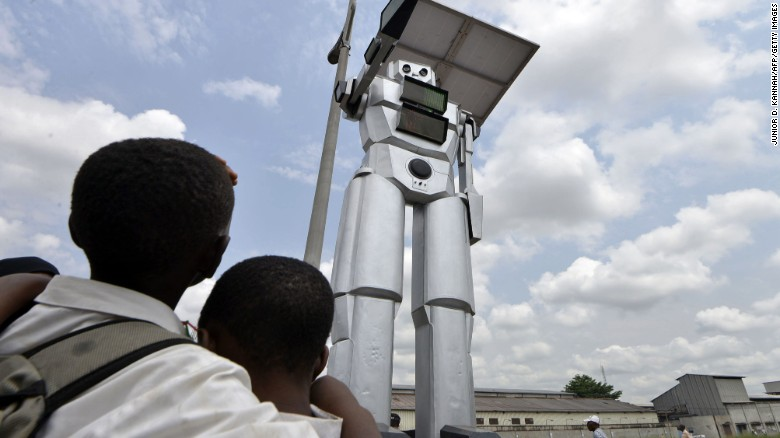 This picture taken on January 22, 2014 shows a traffic robot cop on Triomphal boulevard of Kinshasa at the crossing of Asosa, Huileries and Patrice Lubumba streets. Two human-like robots were recently installed here to help tackle the hectic traffic usually experienced in the area. The prototypes are equipped with four cameras that allow them to record traffic flow, the information is then transmitted to a center where traffic infractions can be analyzed. The team behind the new robots are a group of Congolese engineers based at the Kinshasa Higher Institute of Applied Technique, known by its French acronym, ISTA.