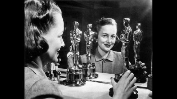 """<strong>Olivia de Havilland (1950):</strong> Olivia de Havilland looks at her two best actress Oscars. She won her second in 1950 for her role in """"The Heiress."""""""