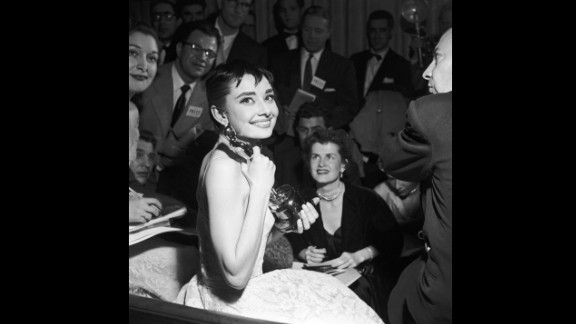 """<strong>Audrey Hepburn (1954):</strong> Audrey Hepburn is surrounded by reporters as she holds her best actress Oscar for """"Roman Holiday."""""""