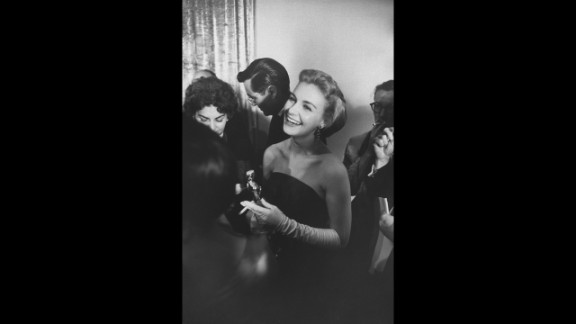 """<strong>Joanne Woodward (1958):</strong> Joanne Woodward smiles while holding her best actress Oscar (and a cigarette). She received the award for her role in the film """"Three Faces of Eve."""""""