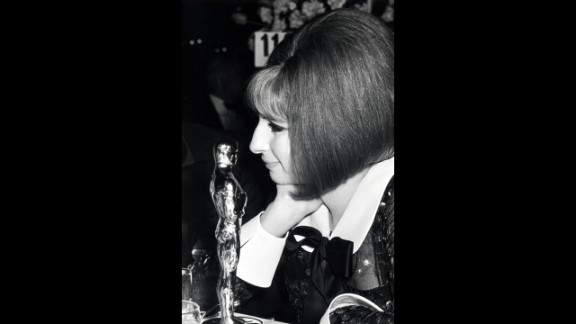 """<strong>Barbra Streisand (1969):</strong> Barbra Streisand gazes at the best actress statuette she won for """"Funny Girl."""" There was a tie for the award in 1969, with the other winner being Katharine Hepburn."""