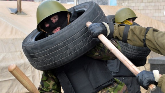 Maidan self-defence activists fight during a drill in a camp of the Ukrainian anti-government opposition on Independence Square in Kiev on February 17, 2014.