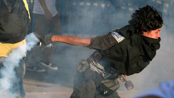 A student protester returns a tear gas canister to riot police on February 15 in Caracas.