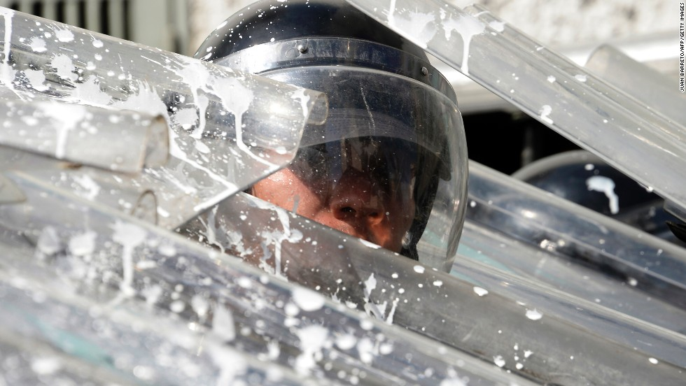 Riot police protect themselves during an opposition rally in Caracas on February 12.