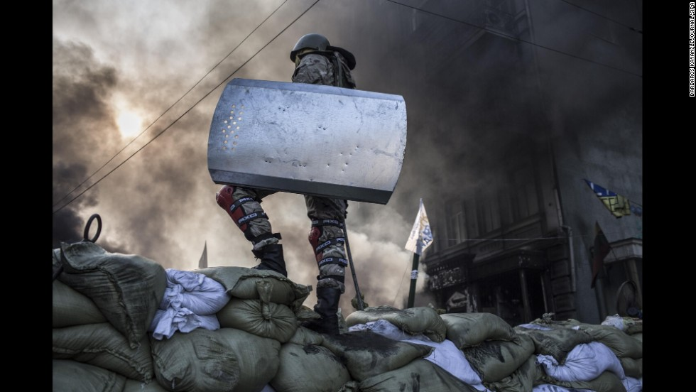 A protester stands atop a barricade in Kiev on February 18.