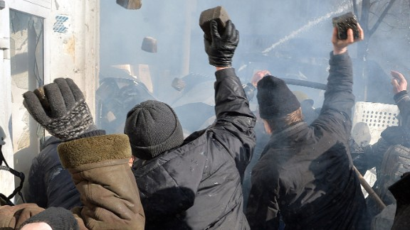 Anti-government protesters throw rocks during clashes with police in front of the Ukrainian Parliment in Kiev on February 18, 2014. At least three anti-government protesters were killed and some 150 others injured, some seriously, today in fresh clashes between police and demonstrators protesting near Ukraine