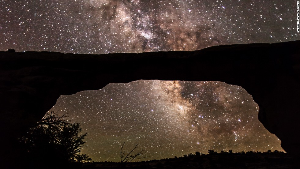 "<strong>Natural Bridges National Monument (Utah): </strong>The natural Owachomo Bridge in Utah is silhouetted against the Milky Way and thousands of stars. This photo was taken on a particularly clear night after a storm, and features potholes full of water reflecting the scene, says photographer <a href=""http://jwfrank.com"" target=""_blank"">Jacob Frank</a>."