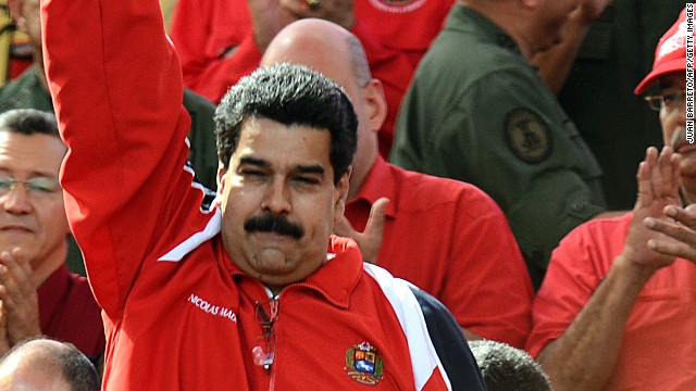 Venezuelan Vice-President Nicolas Maduro raises his fist as he delivers a speech during a massive gathering in homage of Venezuelan President Hugo Chavez in front of Miraflores presidential palace in Caracas on January 10, 2013. With cancer-stricken President Hugo Chavez hospitalized in Cuba, thousands of flag-waving Venezuelans in red shirts filled the streets of Caracas Thursday to inaugurate his new term without him. Bands played anthems from street-side stages as people poured out of buses to make their way on foot toward the Miraflores presidential palace for a symbolic swearing-in of the people in place of Chavez, who is too sick to take the oath of office. AFP PHOTO/Juan BARRETO (Photo credit should read JUAN BARRETO/AFP/Getty Images)