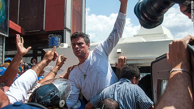 Leopoldo Lopez (C), an ardent opponent of Venezuela's socialist government facing an arrest warrant after President Nicolas Maduro ordered his arrest on charges of homicide and inciting violence, is escorted by the national guard into a vehicle after he turned himself in, during a demonstration in Caracas, on February 18, 2014. Fugitive Venezuelan opposition leader Lopez, blamed by Maduro for violent clashes that left three people dead last week, appeared at an anti-government rally in eastern Caracas and quickly surrendered to the National Guard after delivering a brief speech. AFP PHOTO / CRISTIAN HERNANDEZCRISTIAN HERNANDEZ/AFP/Getty Images