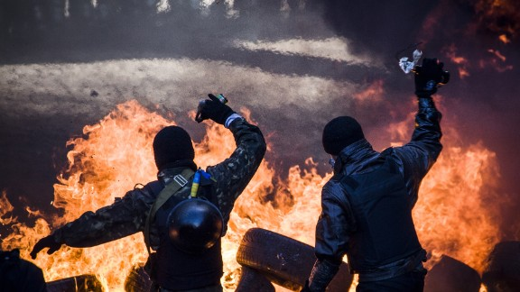Anti-government demonstrators clash with riot police in central Kiev on February 18,