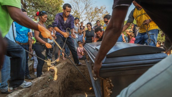 """The casket is lowered at a funeral for a 49-year-old sugar cane worker in Chichigalpa, Nicaragua. Mortality rates from chronic kidney disease in La Isla community are so high that it is now called La Isla de Viudas, or """"The Island of Widows."""""""