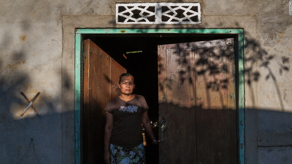 A widow stands in the doorway of her home. She lost her husband and two brothers to kidney disease.