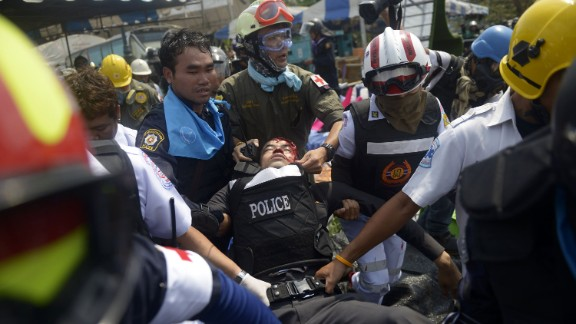 BANGKOK, THAILAND - FEBRUARY 18: A Police officer is carried to an ambulance after he was shot in the head by sniper fire during a police operation to reclaim the protest site at Phan Fa Bridge on February 18, 2014 in Bangkok, Thailand. Thai police tried to reclaim an area of land which anti government protesters have been occupying for the last few weeks but during the confrontation, police had to withdraw allowing the protesters back into the protest site. The recent controversial elections exposed an increasingly bitter divide in the country. After disrupting the general election, anti-government demonstrators are continuing their campaign to oust Prime Minister Yingluck Shinawatra and the three week old 'Bangkok Shutdown, ' has blocked major intersections. The Thai government imposed a 60-day state of emergency in Bangkok and the surrounding provinces in an attempt to cope with the on-going political turmoil however this decree has had no effect on the mass protests. (Photo by Nick McGrath/Getty Images)
