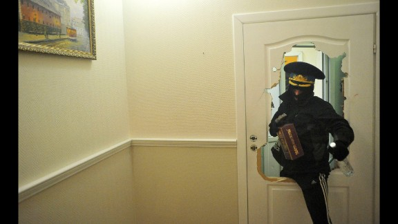 A protester rushes through a broken door in the regional prosecutor