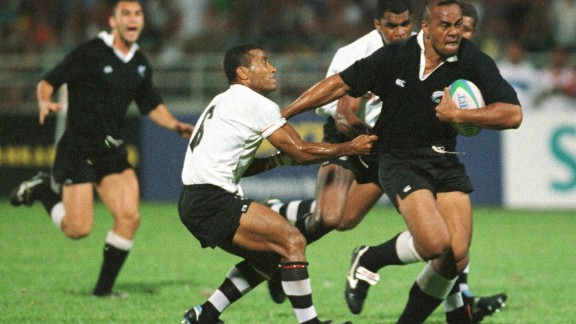 """Lomu in action during the 1998 Commonwealth Games against Fiji, where not even the great Waisale Serevi (left) can stop him. New Zealand would go on to take the gold medal. Lomu was a passionate advocate of sevens: """"The greatest thing I love about it is the camaraderie that the players have among all the nations ... that come together to make this beautiful game."""""""