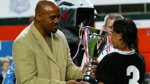 Lomu's last international match was in late 2002, but after his kidney transplant he played club rugby sporadically until 2010. Here Lomu presents Annie Brown of New Zealand with the Women's Rugby Sevens trophy during the 2004 Hong Kong Sevens.