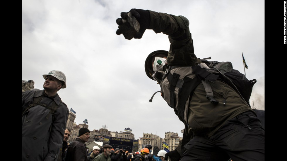 A protester throws a cobblestone at riot police during clashes in Independence Square on February 19.