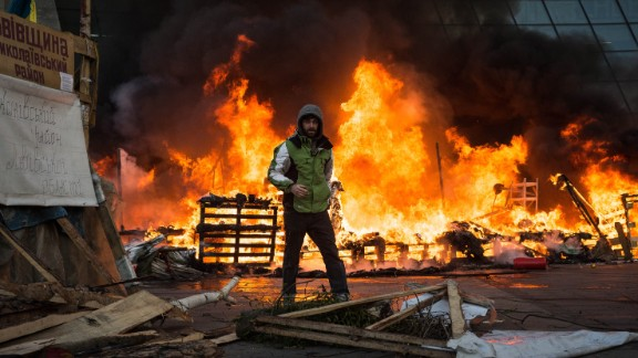 A Ukrainian protester stands in front of the burning Euromaidan protest camp in Kiev on Wednesday February 18. Protesters set up tents in the square in December, says iReporter and American journalist Chris Collison.