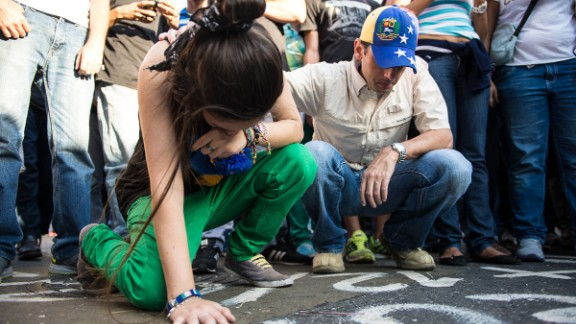 A young woman cries on February 13 at the place where one of the opposition members was killed a day before in Caracas.