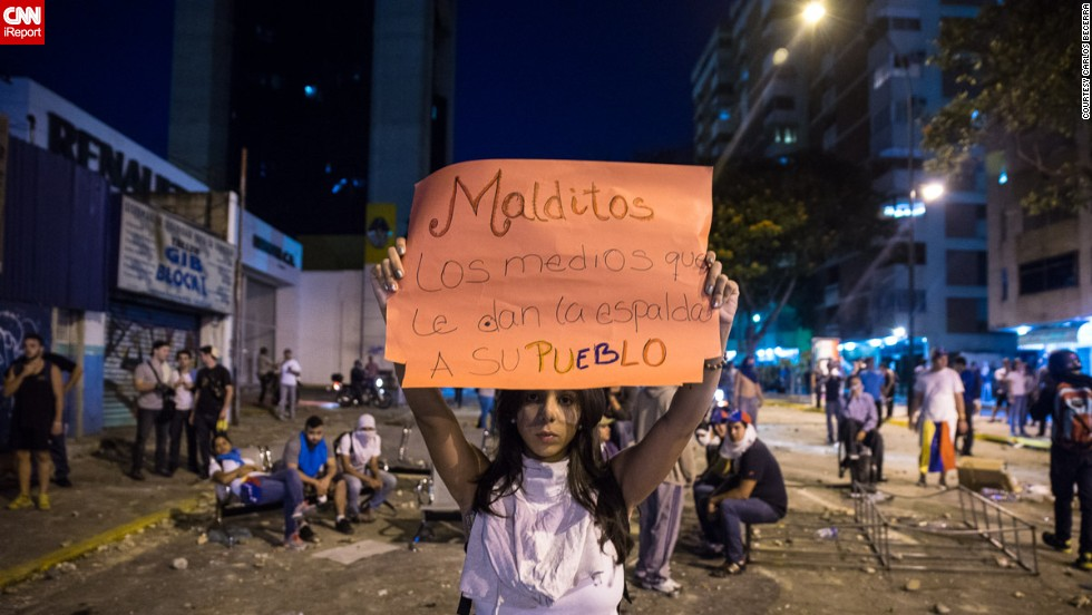 """Damned are the media that give its people the cold shoulder,"" reads a <a href=""http://ireport.cnn.com/docs/DOC-1086189"">sign held by a student </a>protesting in Caracas on February 15. Protesters say national media are not reporting about the protests and the violence."