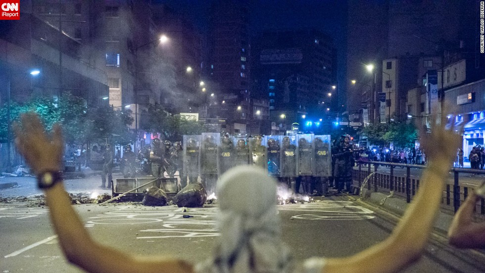 "A protester in Caracas stands in front of a ""piquete,"" a National Guard picket. Freelance photographer Carlos Becerra captured this image on February 15."