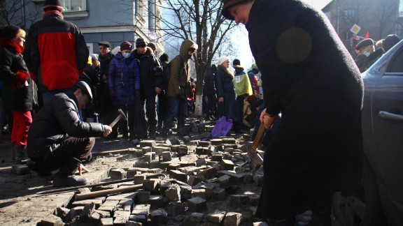 """A woman on a Kiev street digs up pavement bricks to be used as weapons by pro-Europe demonstrators. Ukrainian student Oleksandr Guzenko said he was fascinated by """"how motivated and brave [protesters] were to stand there and make a change, support and contribute."""""""