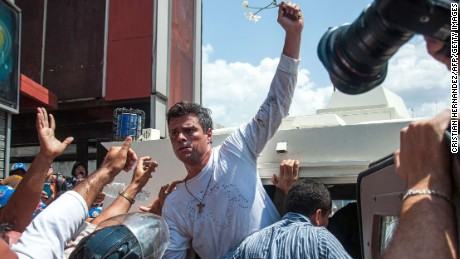 Leopoldo Lopez (C), an ardent opponent of Venezuela's socialist government facing an arrest warrant after President Nicolas Maduro ordered his arrest on charges of homicide and inciting violence, is escorted by the national guard into a vehicle after he turned himself in, during a demonstration in Caracas, on February 18, 2014.