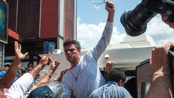 Leopoldo Lopez (C), an ardent opponent of Venezuela's socialist government facing an arrest warrant after President Nicolas Maduro ordered his arrest on charges of homicide and inciting violence, is escorted by the national guard into a vehicle after he turned himself in, during a demonstration in Caracas, on February 18, 2014. (CRISTIAN HERNANDEZ/AFP/Getty Images)