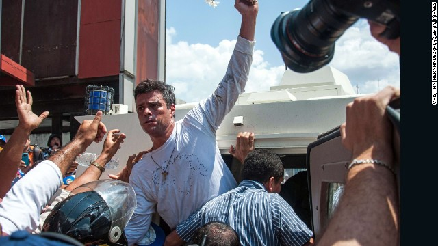 Leopoldo Lopez (C), an ardent opponent of Venezuela's socialist government facing an arrest warrant after President Nicolas Maduro ordered his arrest on charges of homicide and inciting violence, is escorted by the national guard into a vehicle after he turned himself in, during a demonstration in Caracas, on February 18, 2014. Fugitive Venezuelan opposition leader Lopez, blamed by Maduro for violent clashes that left three people dead last week, appeared at an anti-government rally in eastern Caracas and quickly surrendered to the National Guard after delivering a brief speech. AFP PHOTO / CRISTIAN HERNANDEZ        (Photo credit should read CRISTIAN HERNANDEZ/AFP/Getty Images)