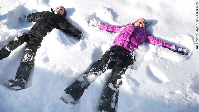 Parker Miller, 9, left, and his sister Madigan, 11, children of Troy and Amy Miller, make snow angels in there yard on Woodlawn Ave. in Beckley, W.Va. Friday morning, Feb. 14, 2014. (AP Photo/The Register-Herald, Rick Barbero)