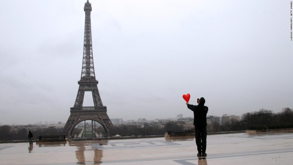During Valentine's Day celebrations on February 14, a man takes a picture of a red heart in front of the Eiffel Tower in Paris.