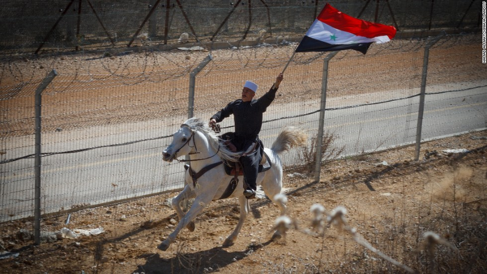 A man riding a horse waves a Syrian flag during a rally on February 14 in Majdal Shams, a Druze village on the border between the Israeli-occupied Golan Heights and Syria.
