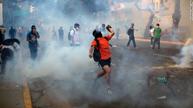 Protesters throw objects amid tear gas launched by riot police in the Altamira neighborhood of Caracas on February 19.