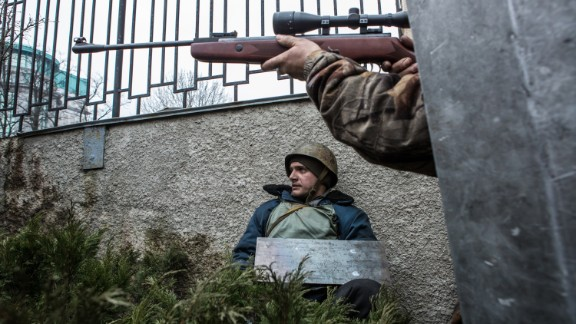 A Ukrainian protester aims a gun in the direction of suspected sniper fire near the Hotel Ukraine in Kiev on Thursday, February 20.