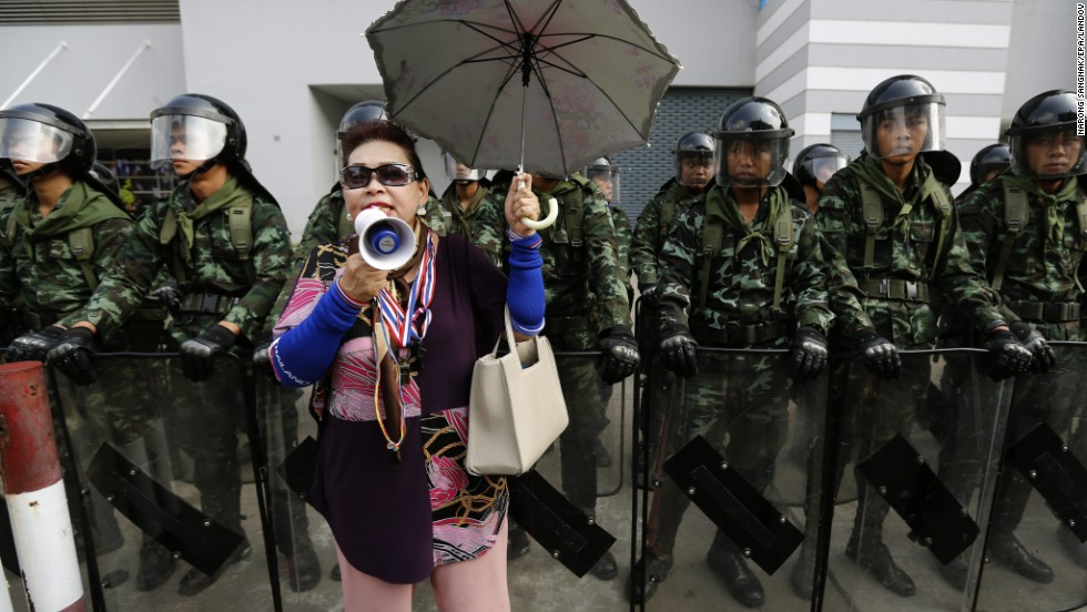A protester shouts slogans in front of Thai army soldiers on guard during a rally in front of the temporary office of the prime minister at the defense ministry complex in Bangkok on Wednesday, February 19.