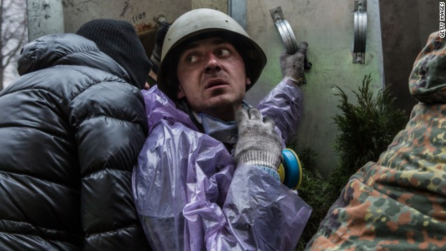 An anti-government protester takes cover from suspected sniper fire near the Hotel Ukraine on February 20, 2014 in Kiev, Ukraine.