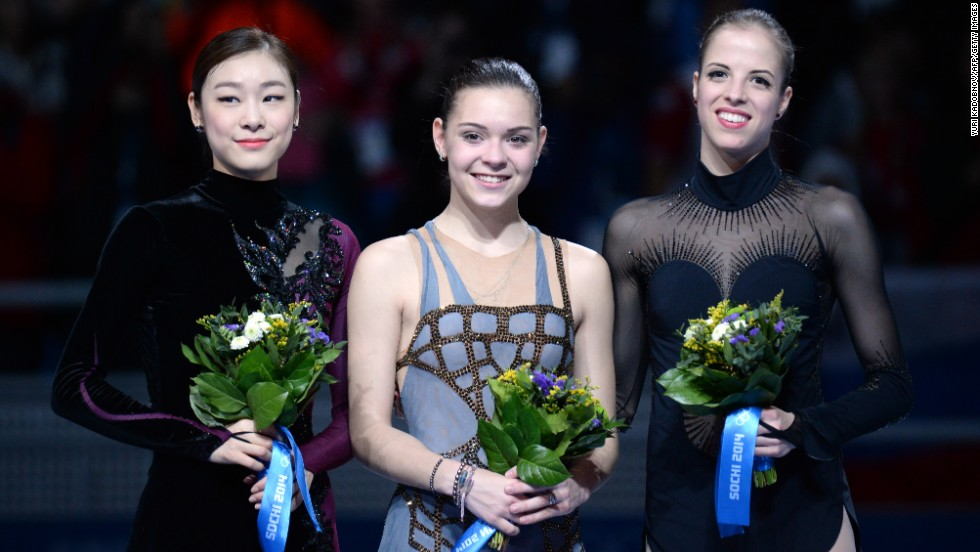 Kim, left, and Sotnikova were accompanied by bronze medalist Carolina Kostner of Italy during the flower ceremony.