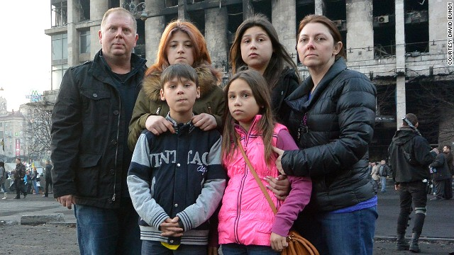David Bundy, left, stands in Kiev's Independence Square with his wife Lisa, right, and the four orphans they are adopting.