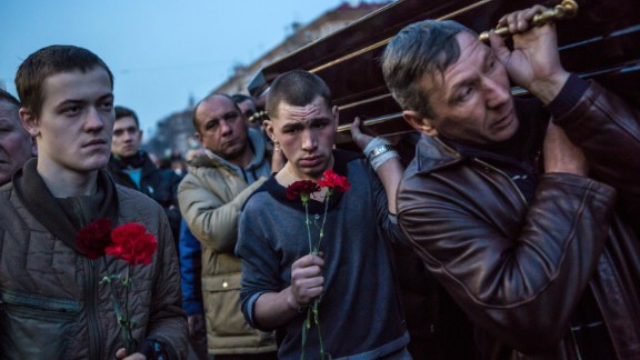 Men in Kiev carry a casket containing the body of a protester killed in clashes with police.