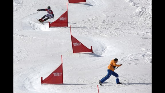 Russia's Vic Wild takes a turn as a course worker runs to get out of the way during a the snowboard parallel slalom quarterfinal on February 22.