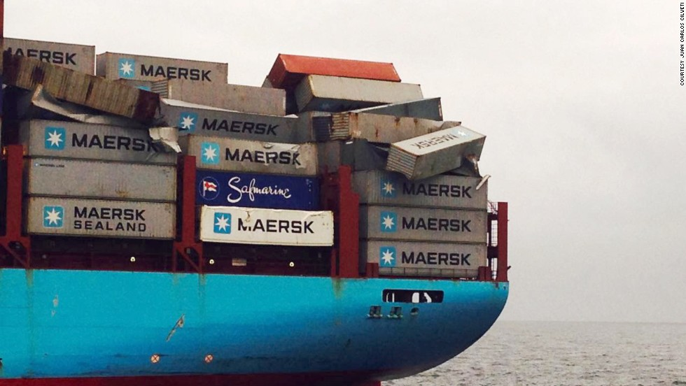Containers lay damaged and precariously perched on the deck of the ship.