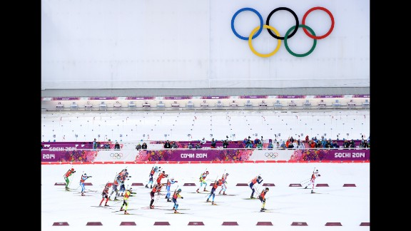 Skiers pass the Olympic rings as they compete during the men