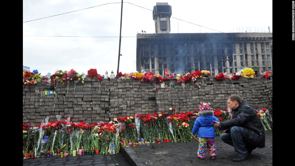 A man and his daughter lay flowers at a memorial for protesters killed in Independence Square.