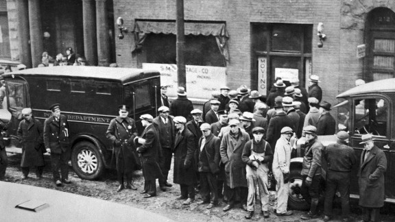 Police and spectators gather in front of the garage on Chicago's North Clark Street, where members of Al Capone's gang, disguised as policemen, shot and killed seven members of a rival gang on February 14, 1929. The St. Valentine's Day Massacre became a symbol of the extreme violence of the Chicago underworld and crime boss Al Capone.